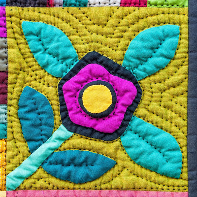 Voici un bloc d'un des derniers quilts de Nifty Quilts : tout est matelassé au fil noir ! L'ensemble est d'une grande énergie, mêlant folk art et modernité. Le quilt entier, avec d'autres vues de détail, est visible par ici.